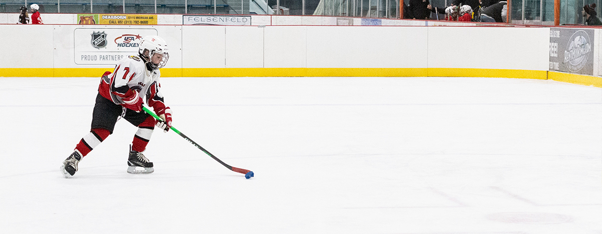 Photo of a 8U Dearborn Hockey player skating with his stick and puck